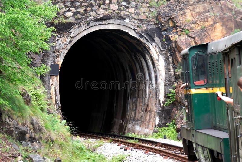Zug mit den pasengers, die zum Tunnel im Berg gehen stockbilder