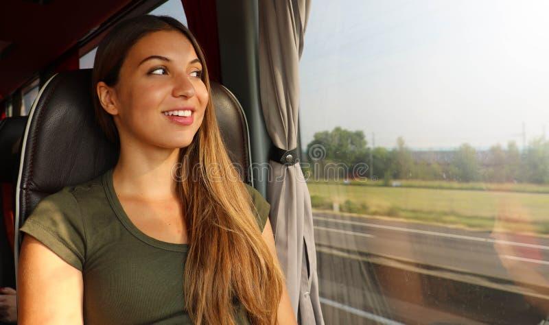 Zug- oder Busreise Schöne lächelnde Frau, die durch das Fenster während der Reise auf öffentlichem Transport schaut stockfoto