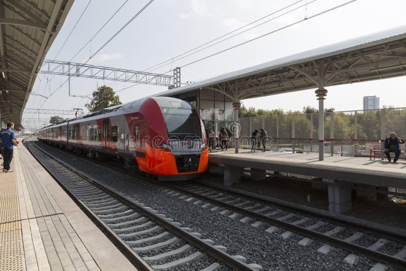 Zug-Schwalbe kommt im Passagierplattformstation botanischen Garten des Moskau-Zentralringes an stockfotografie