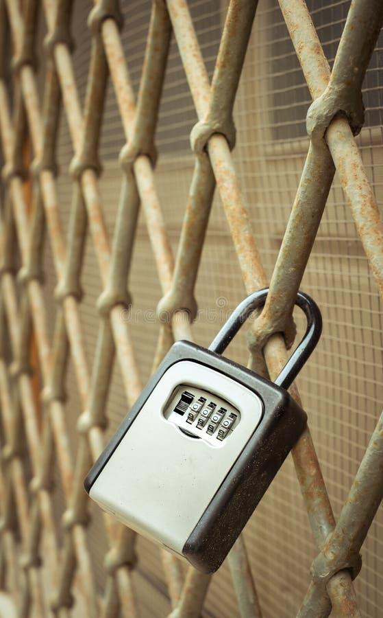 Zugeschlossen mit einem modernen Schlüssel auf einem alten Gitter lizenzfreies stockbild