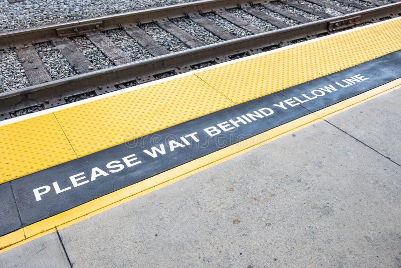 Zugplattform mit Zeichen warten bitte hinter die gelbe Linie und den gelben markierten warnenden Bereich stockbilder