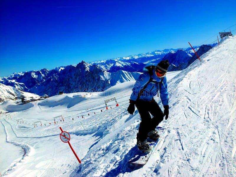 Zugspitze Tyskland -21 Februari 2012: Kvinnan som snwoboarding i fjällängar, snöar berg under skidar och snowboardferie royaltyfri foto