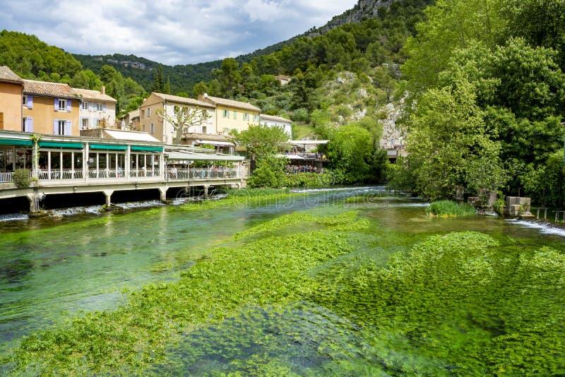 Zuiden van Frankrijk, mening op kleine Provencal-stad van dichter Petrarch fontaine-DE-Vaucluse met smaragdgroene wateren van Sor stock afbeeldingen