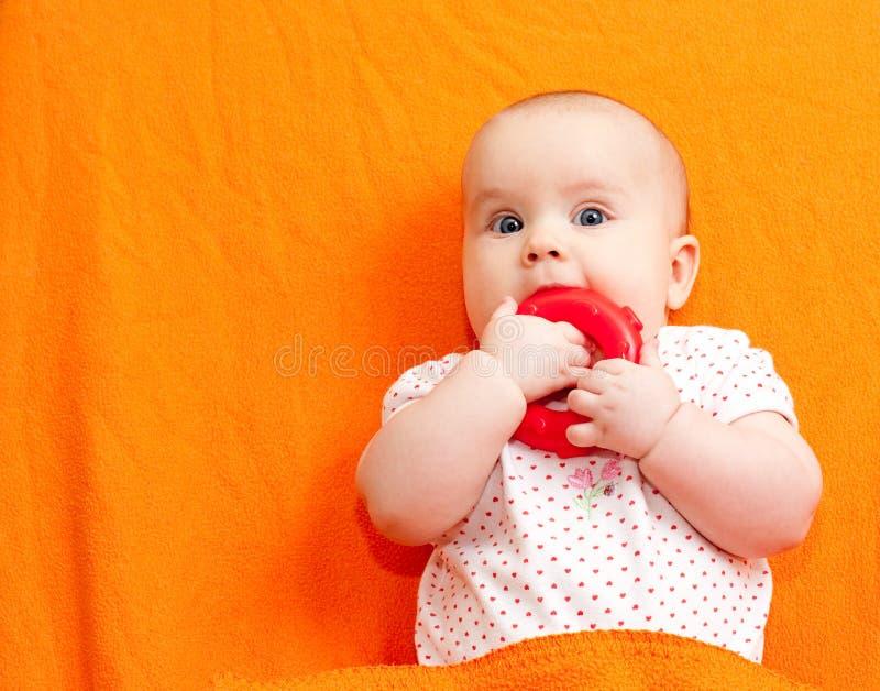 Zuigeling met tandjes krijgenstuk speelgoed stock foto's