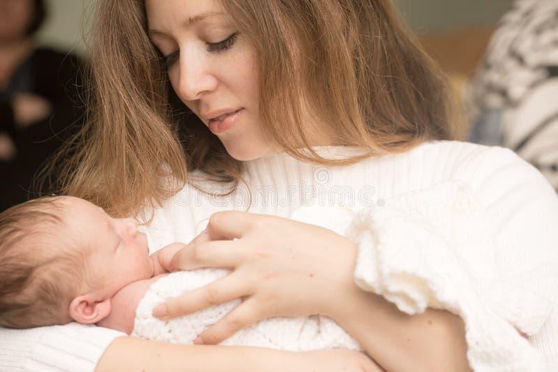 Zuigelingsjongen op de moederhanden stock afbeeldingen