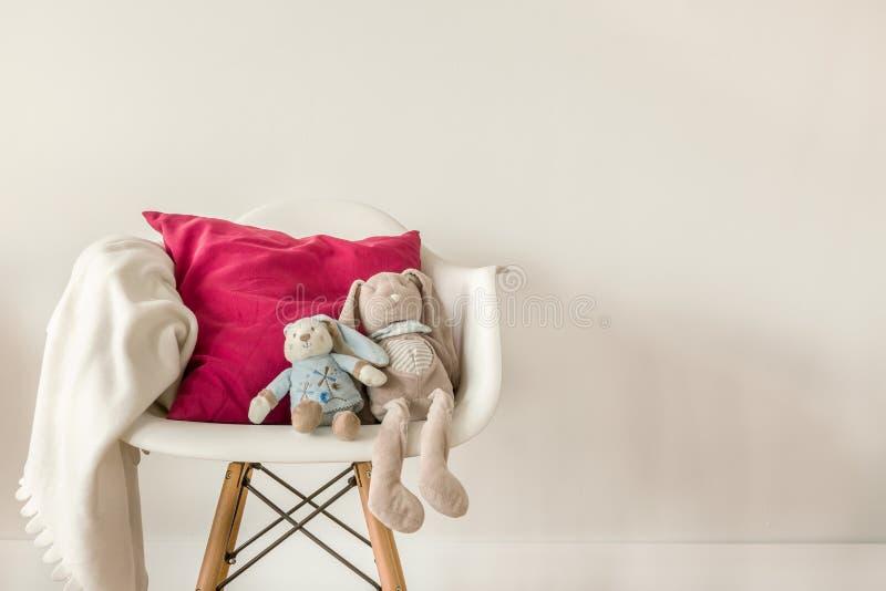Zuigelingstoebehoren op witte stoel stock afbeeldingen