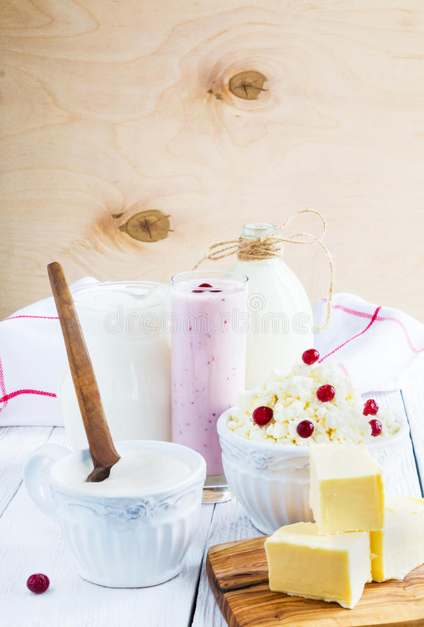 Zuivelopbrengst Melk in fles, kwark in kom, kefir in kruik, Amerikaanse veenbesyoghurt in glas, boter en verse bessen Houten w stock afbeeldingen