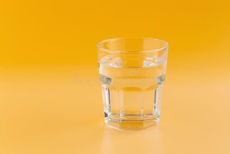 Zuiver water in een glas op een oranje achtergrond stock afbeelding