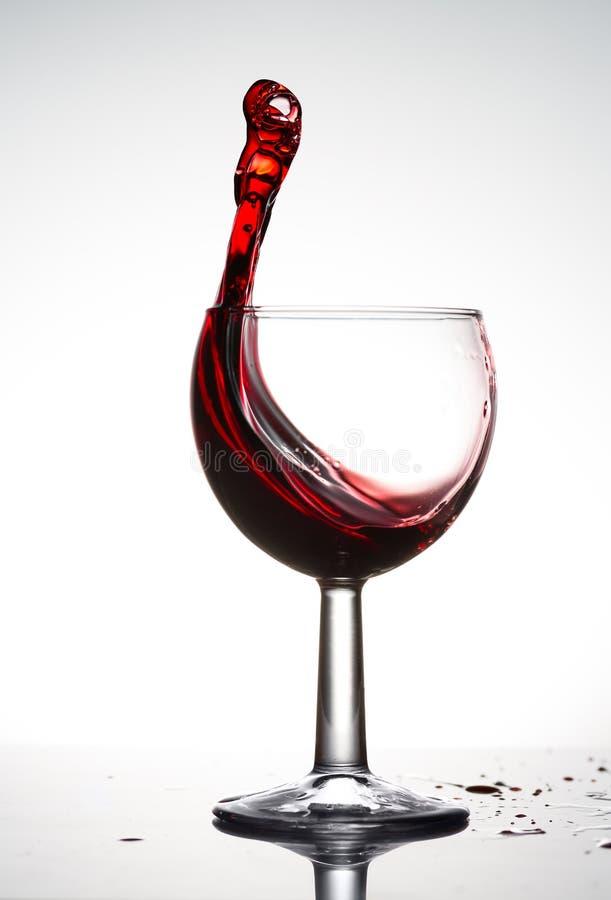 Zuiver wijnglas met golf van helder rode wijn op witte achtergrond stock afbeelding