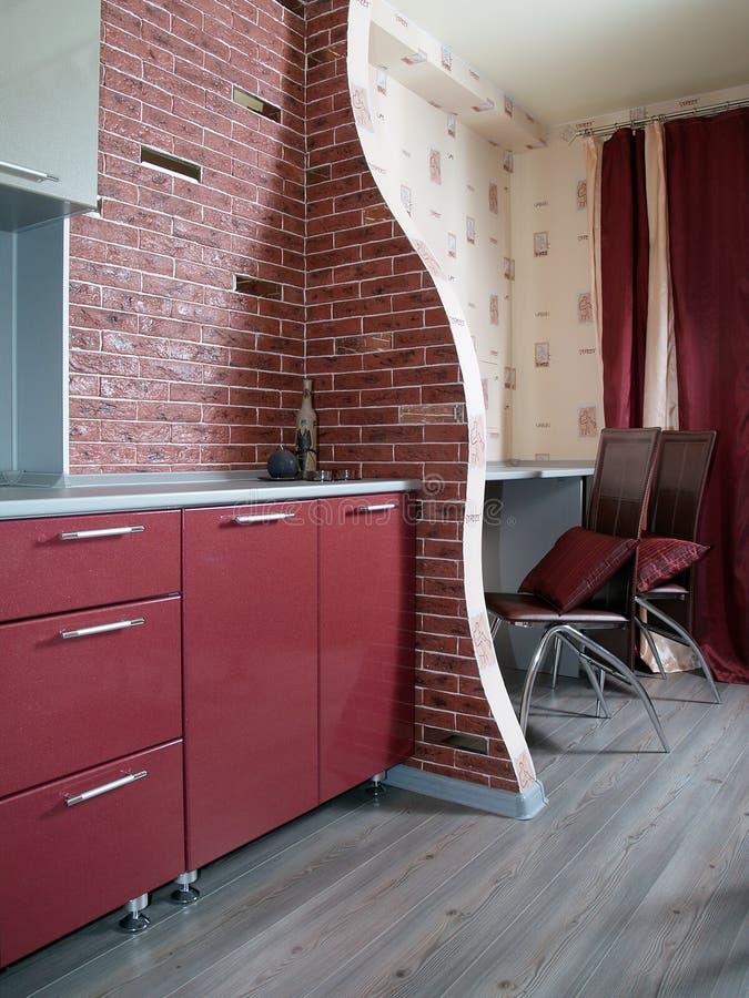 Zuivere moderne rode keuken met een bakstenen muur stock fotografie