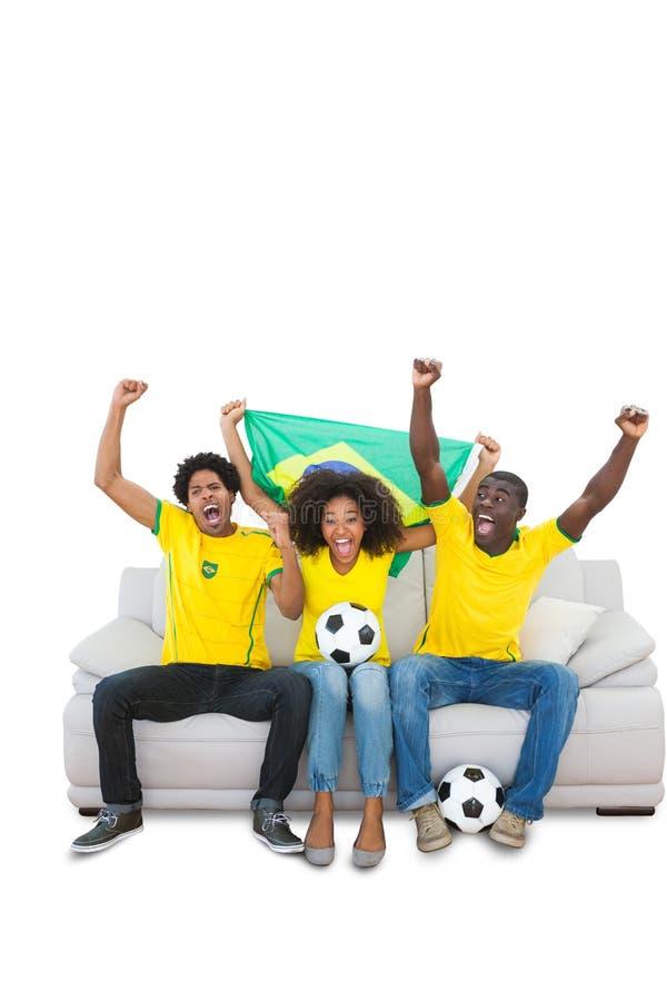 Zujubelnde brasilianische Fußballfane im Gelb auf dem Sofa stockfoto