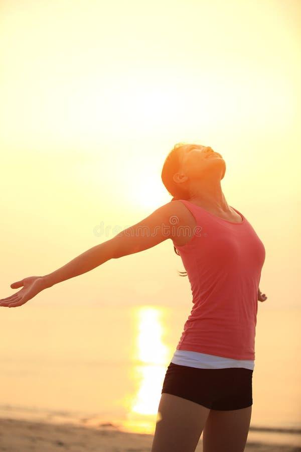 Zujubelnde Frau öffnen Arme auf Strand lizenzfreie stockfotos