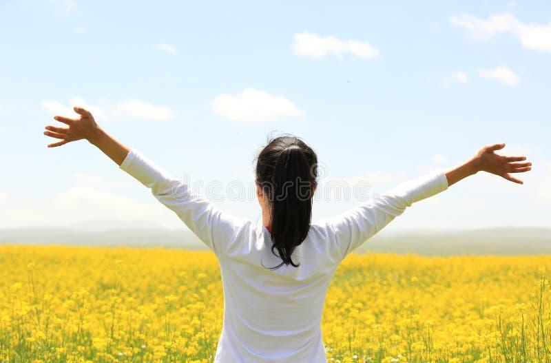 Zujubelnde Frau öffnen Arme am Coleblumenfeld lizenzfreies stockfoto