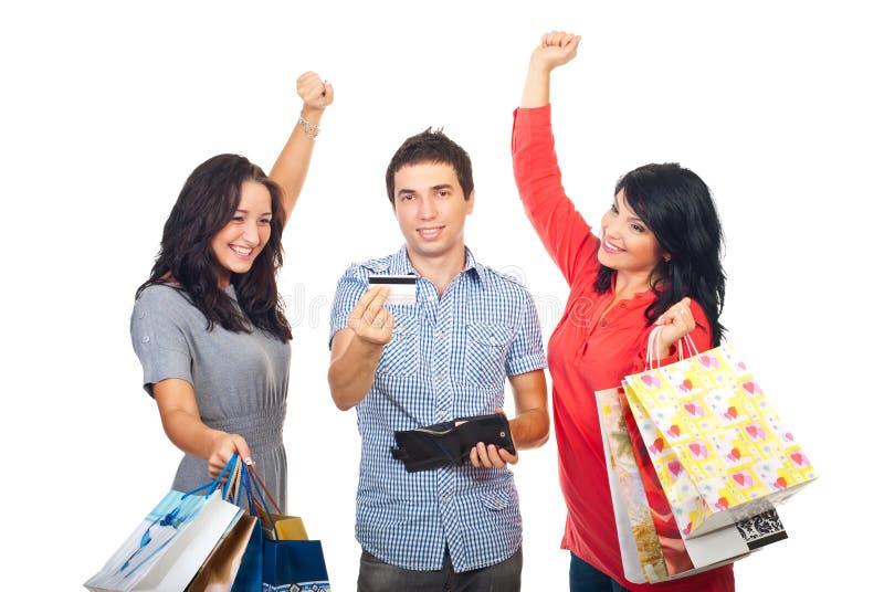Zujubelnde Freunde mit Kreditkarte und den Einkaufen stockfotografie