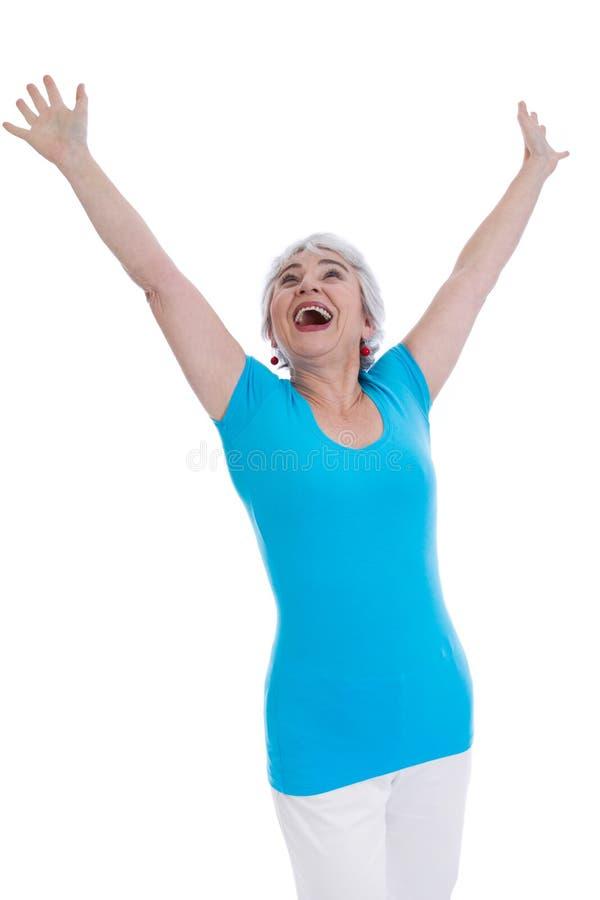 Zujubelnde glückliche ältere Frau lokalisiert in einem blauen Hemd. lizenzfreie stockbilder