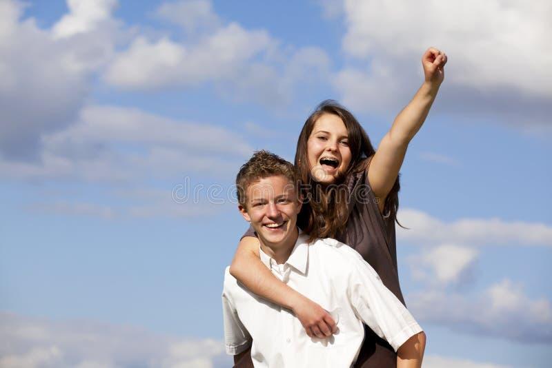 Zujubelnde glückliche Jugendpaare stockfotografie