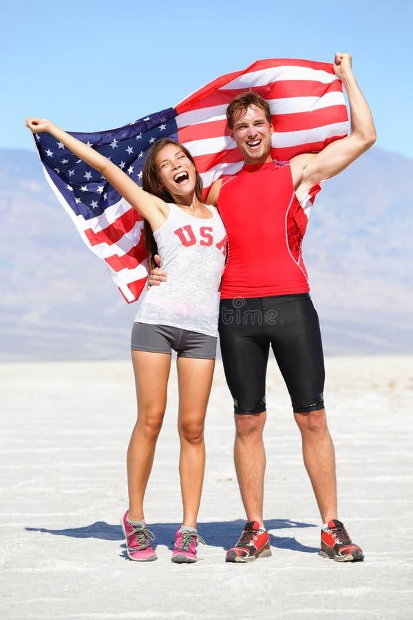 Zujubelnde Leuteathleten, die amerikanische USA-Flagge halten lizenzfreies stockfoto