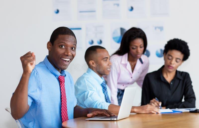 Zujubelnder Afroamerikanergeschäftsmann mit Geschäftsteam im Büro stockfotos