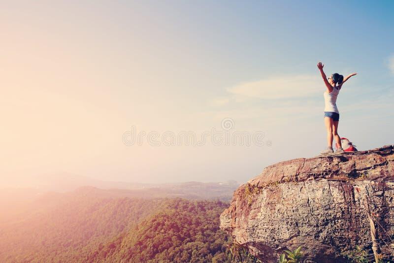 Zujubelnder Frauenwanderer öffnen Arme an der Bergspitze stockfotos