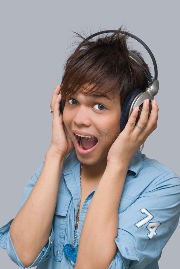 Zujubelnder Junge mit Kopfhörern stockfotos
