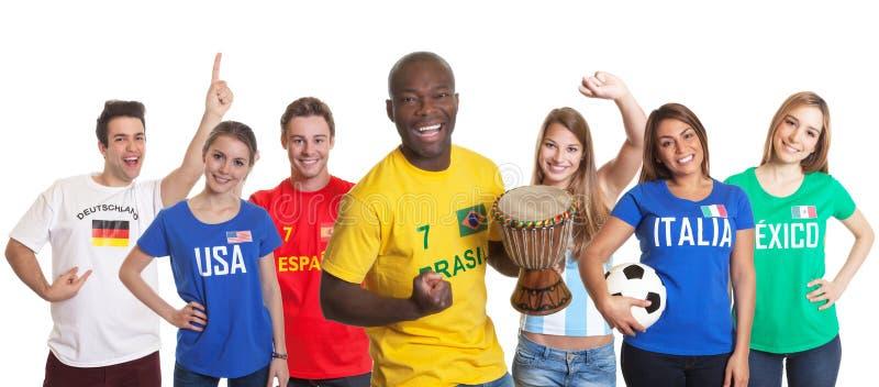 Zujubelndes brasilianisches Fußballfan mit Trommel und anderen Fans stockfoto