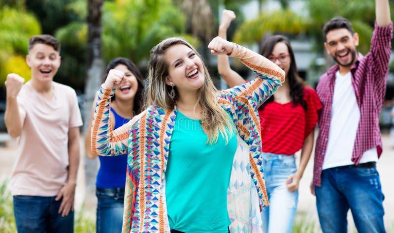 Zujubelndes deutsches Mädchen mit glücklicher Gruppe Freunden stockbilder