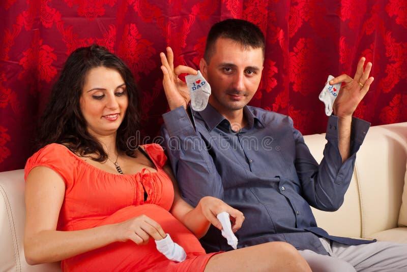 Zukünftige Muttergesellschaft, die babys Tücher zeigen stockbilder
