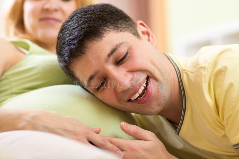 Zukünftiger Vater, der auf Bauch seiner schwangeren Frau hört lizenzfreies stockfoto
