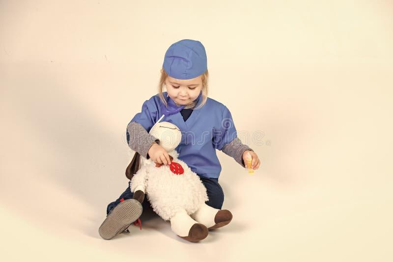Zukunft von Veterinärmedizin Kleiner Junge in einheitlichem spielendem Tierarzt Doktors mit Spielzeugtier lizenzfreie stockbilder
