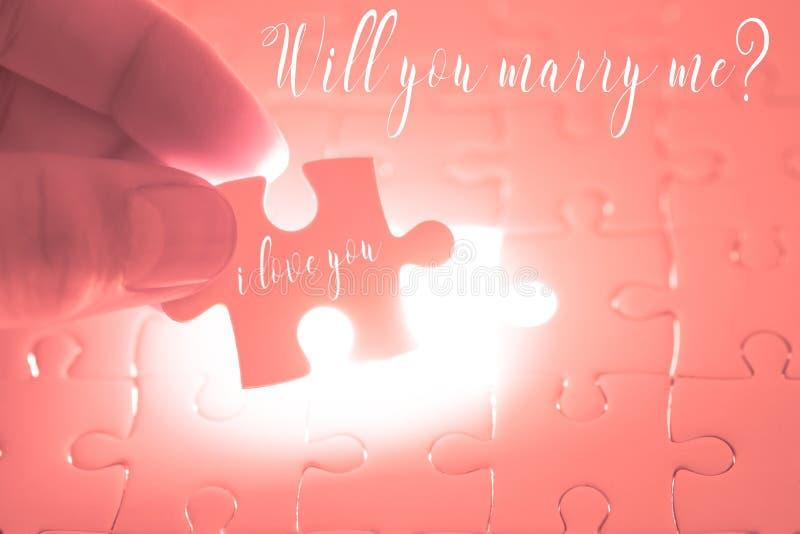 Zult u me woord op roze puzzel huwen die zijn holding door Th royalty-vrije stock fotografie
