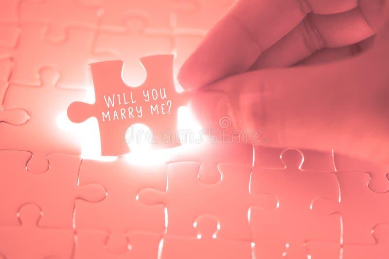 Zult u me woord op roze puzzel huwen die zijn holding door Th stock fotografie
