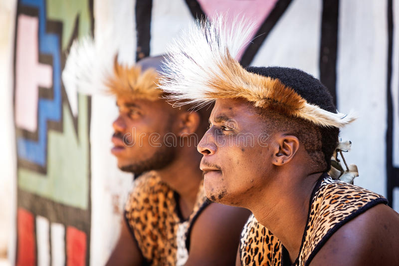 Zulu Warriors Wear Traditional Garments. LESEDI CULTURAL VILLAGE, SOUTH AFRICA - NOVEMBER 4, 2016. Two young male Zulu tribe members wearing traditional warrior stock photo