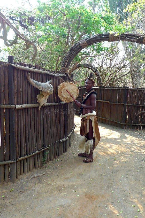 Zulumann in traditionellem schließt Grußtouristen in traditionellem schließt im Shakaland Zulu-Dorf, Südafrika stockbilder