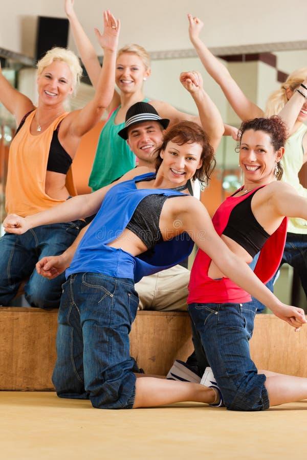 Zumba eller Jazzdance - ungdomarsom dansar i studio arkivbild