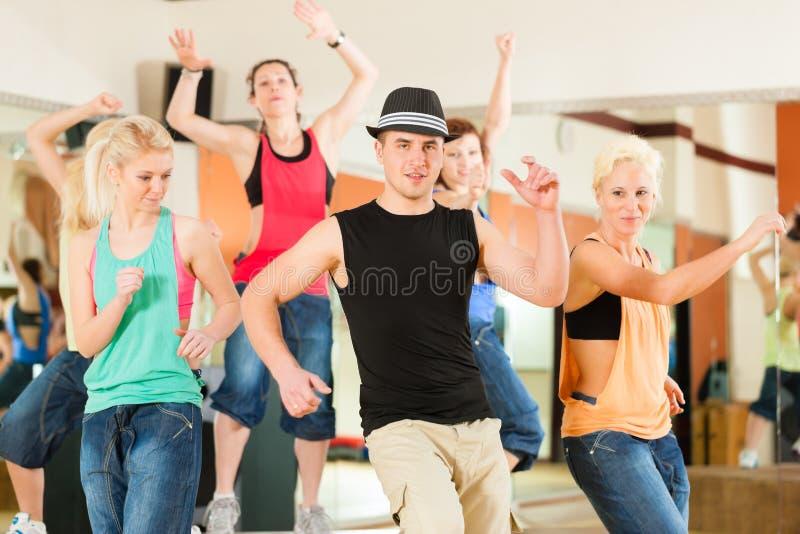 Zumba or Jazzdance - young people dancing in studio royalty free stock photos