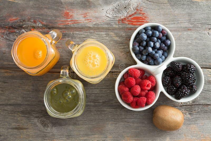 Zumo de fruta fresca con un plato de bayas mezcladas imagen de archivo libre de regalías