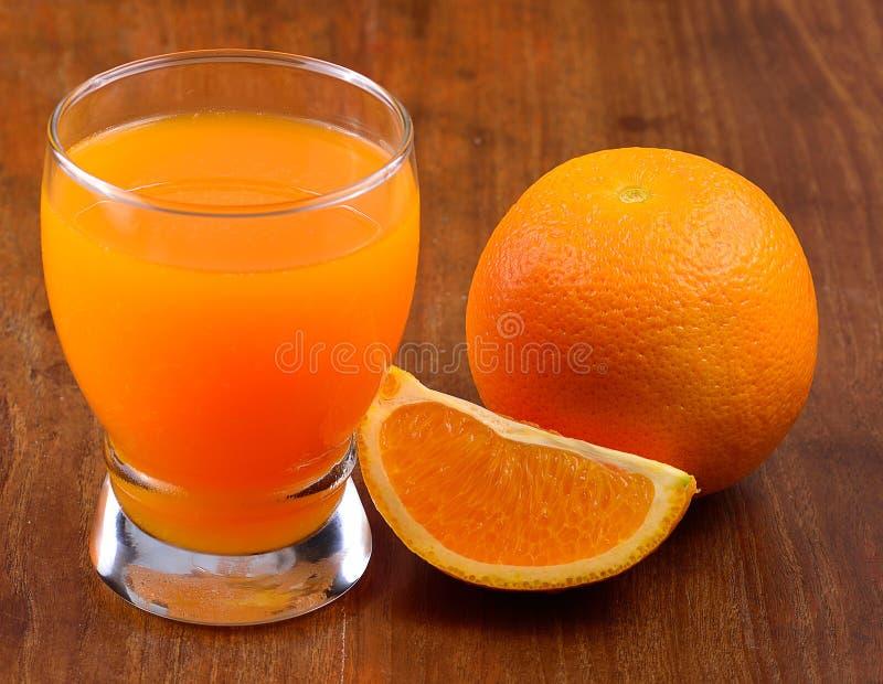 Zumo de naranja aislado en un fondo de madera foto de archivo libre de regalías