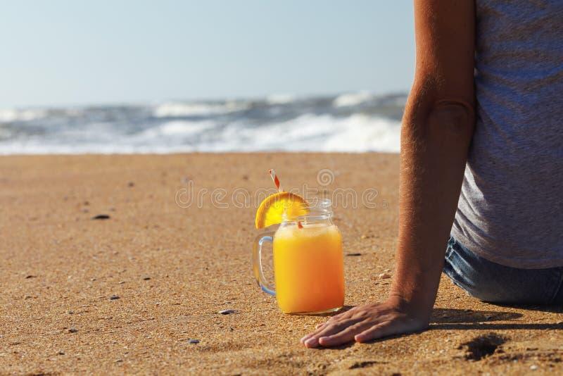 Zumo de naranja con pulpa en un tarro en la playa cerca del turista fotos de archivo libres de regalías