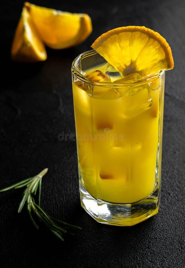 Zumo de naranja de cristal con hielo y rebanadas anaranjadas con la rama del romero en fondo negro foto de archivo