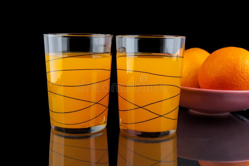 Zumo de naranja - dos vidrios con las naranjas imágenes de archivo libres de regalías
