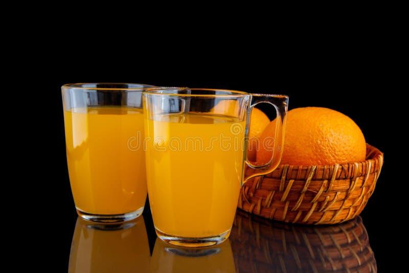 Zumo de naranja - dos vidrios con las naranjas en fondo negro foto de archivo libre de regalías