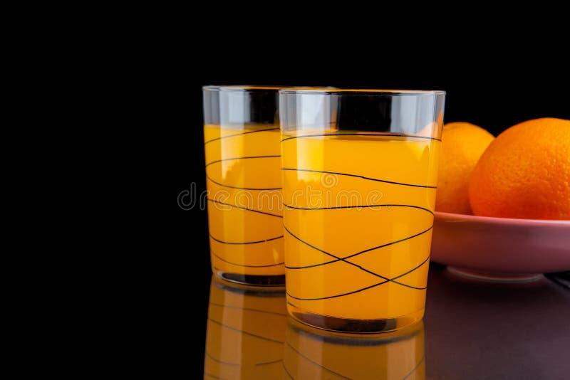 Zumo de naranja - dos vidrios con las naranjas en fondo negro imágenes de archivo libres de regalías