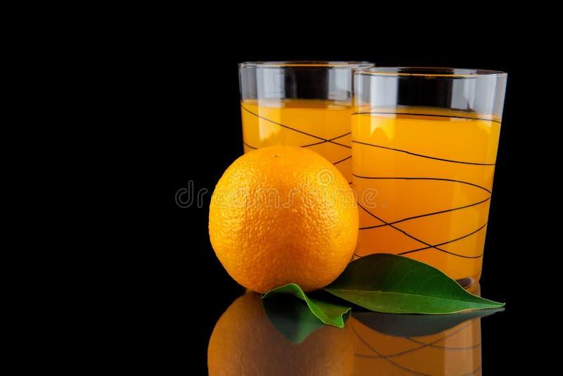 Zumo de naranja - dos vidrios con las naranjas en fondo negro foto de archivo