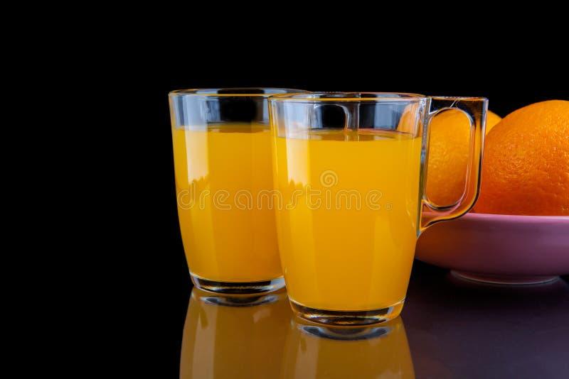 Zumo de naranja - dos vidrios con las naranjas en fondo negro imagenes de archivo