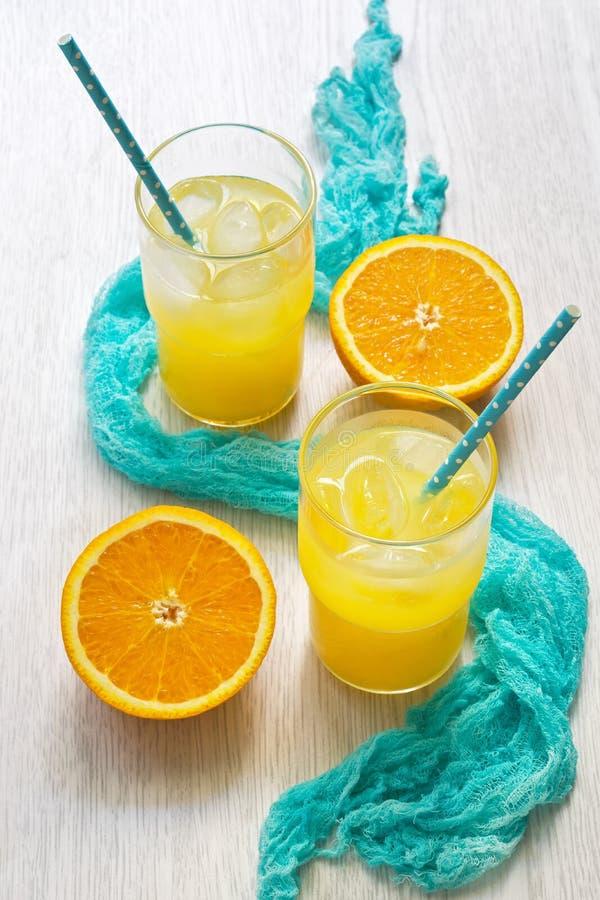Zumo de naranja en un vidrio con una paja en lunares y con una servilleta azul en una tabla de madera blanca El concepto de veran fotografía de archivo libre de regalías