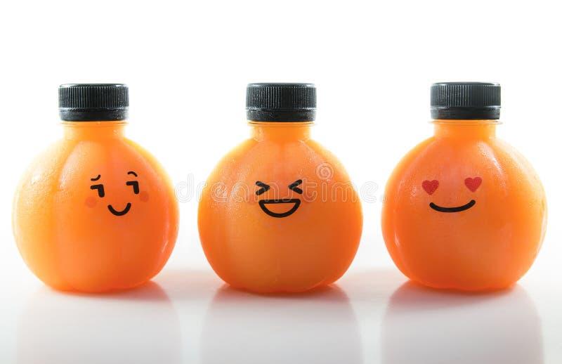 Zumo de naranja en una botella esférica plástica con la cara emocional foto de archivo libre de regalías