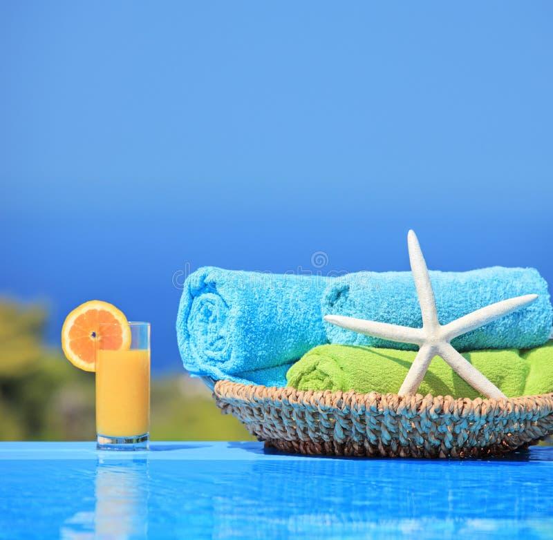 Zumo de naranja, estrellas de mar y toallas al lado de una piscina fotos de archivo libres de regalías