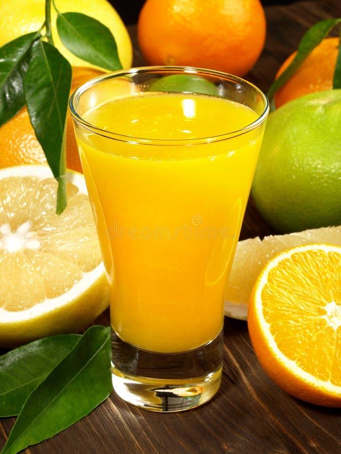 Zumo de naranja fresco con las frutas fotos de archivo