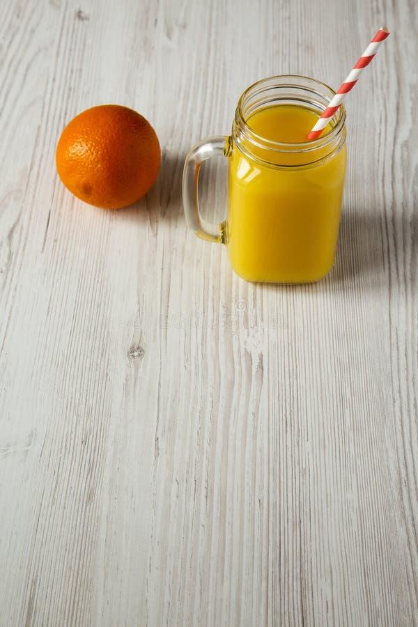 Zumo de naranja fresco en el tarro de cristal sobre el fondo de madera blanco, opinión de ángulo bajo Copie el espacio imagen de archivo