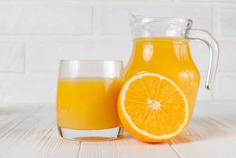 Zumo de naranja fresco en el vidrio y el jarro, mitad de la fruta cítrica en el fondo de madera blanco Consumición sana, tema de  fotos de archivo